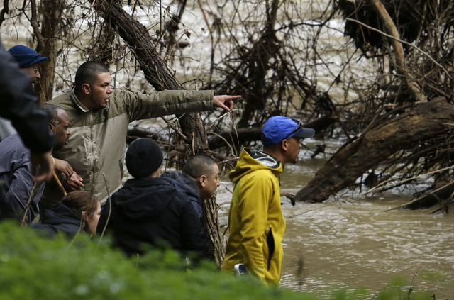 A man points as the parents and friends of a missing 18-year-old woman look at what they believe to be their daughter's submerged car in Alameda Creek on Monday, Jan. 23, 2017, near Fremont, Calif ...