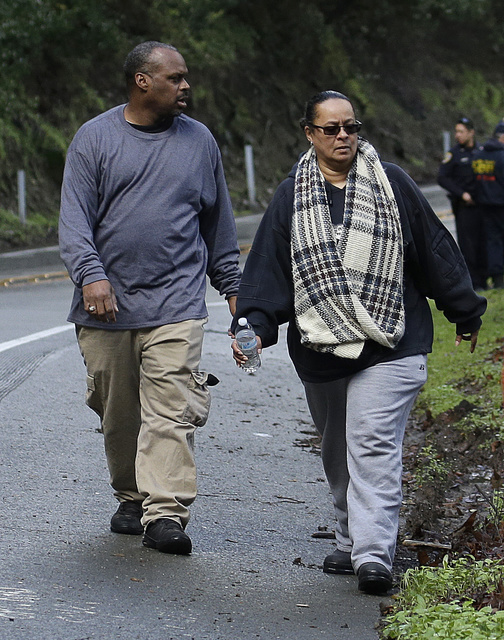 The parents of a missing 18-year-old woman walk along Niles Canyon Road Monday, Jan. 23, 2017, to the scene where their daughter's car careened off the road, near Fremont, Calif. The unidentified  ...