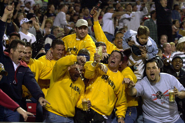 Las Vegas Outlaws fans spill their beer as they cheer during the first half of the XFL game against the New York/New Jersey Hitmen at Sam Boyd Stadium in Las Vegas on Saturday, Feb. 3, 2001.  (AP  ...