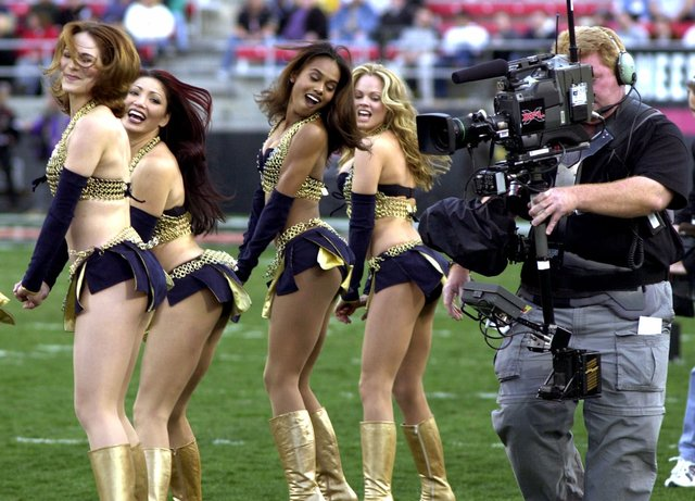 A television cameraman photographs the Los Angeles Xtreme cheerleaders before the start of an XFL game between the Xtreme and the Las Vegas Outlaws, Saturday, Feb. 17, 2001, in Las Vegas. Los Ange ...