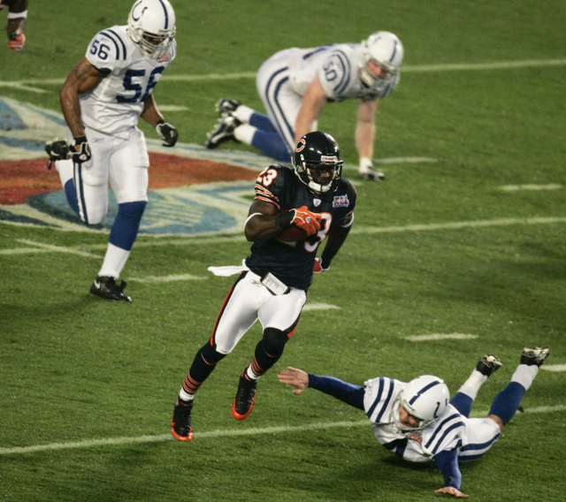 Chicago Bears' Devin Hester (23) returns the opening kick-off for a touchdown as Indianapolis Colts kicker Adam Vinatieri (4) tries to stop him in the first quarter of the Super Bowl XLI football  ...