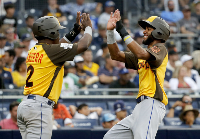 World Team's Amed Rosario, of the New York Mets, right, high fives teammate Dilson Herrera, of the New York Mets, after scoring on an RBI base hit by Raimel Tapia during the ninth inning of the Al ...