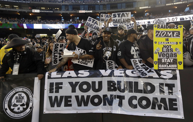 FILE - In this Nov. 6, 2016, file photo, Oakland Raiders fans hold up signs about the team's possible move to Las Vegas during an NFL football game between the Raiders and the Denver Broncos in Oa ...
