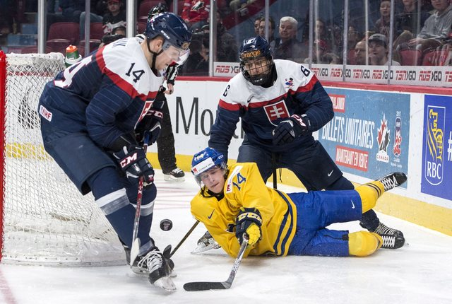 Sweden's Elias Pettersson is hooked by Slovakia's Martin Fehervary in front of Erik Cernak during the first period of a quarterfinal hockey game at the world junior championship in Montreal on Mon ...