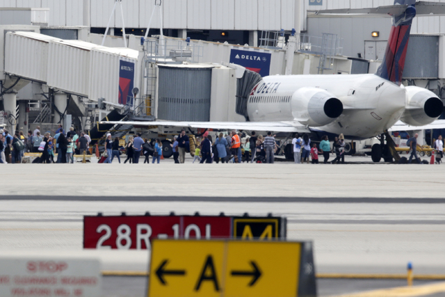 People stand on the tarmac at the Fort Lauderdale-Hollywood International Airport after a shooter opened fire inside the terminal, killing several people and wounding others before being taken int ...
