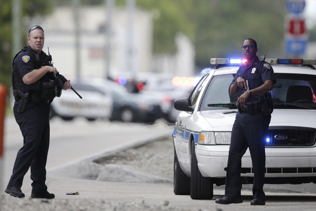 Police officers stand on the perimeter road along the Fort Lauderdale-Hollywood International Airport after a lone shooter opened fire inside a terminal of the airport, killing several people and  ...