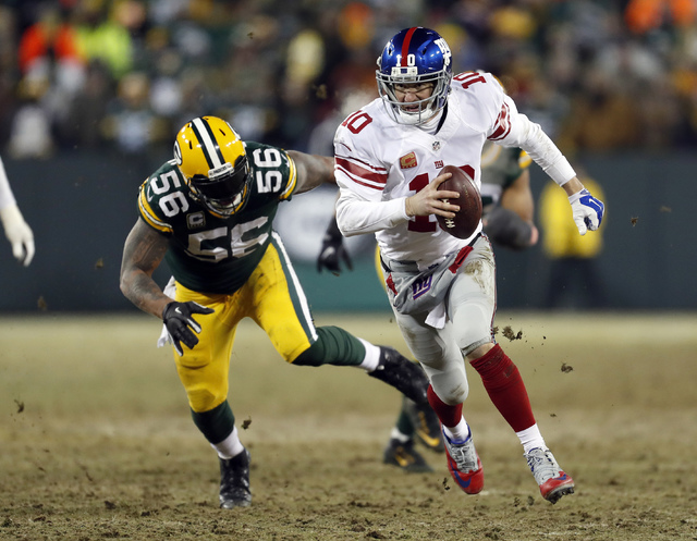 New York Giants quarterback Eli Manning (10) runs against Green Bay Packers outside linebacker Julius Peppers (56) during the second half of an NFC wild-card NFL football game, Sunday, Jan. 8, 201 ...