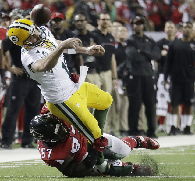 Green Bay Packers' Aaron Rodgers throws while in the grasp of Atlanta Falcons' Grady Jarrett during the second half of the NFL football NFC championship game, Sunday, Jan. 22, 2017, in Atlanta. (A ...