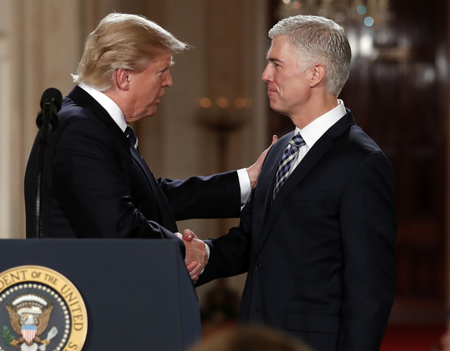 President Donald Trump shakes hands with 10th U.S. Circuit Court of Appeals Judge Neil Gorsuch, his choice for Supreme Court Justices in the East Room of the White House in Washington, Tuesday, Ja ...