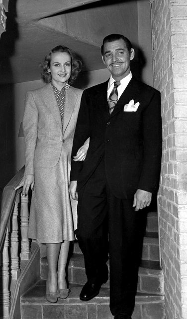 Actor Clark Gable, and his bride Carole Lombard face reporters and photographers March 30,1939 when they returned to Hollywood from their elopement to Kingham Ariz. the day before. The newlyweds a ...