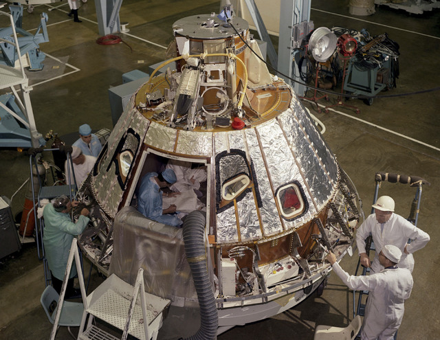 In this 1966 photo made available by NASA, technicians work on the Spacecraft 012 Command Module at Cape Kennedy, Fla., for the Apollo/Saturn 204 mission. (NASA via AP)