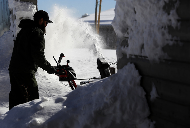 A man clears way with a snow blower at Mount Charleston on Wednesday, Jan. 25, 2017, in Las Vegas.  Clark County announced a voluntary evacuation notice for the Kyle and Lee Canyon areas of Mount  ...