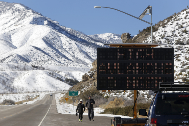 Pedestrians walk to their car near an avalanche warning sign on Highway 157 in Kyle Canyon on Mt. Charleston Wednesday, Jan. 25, 2017. A voluntary evacuation notice was issued Tuesday night for Ky ...