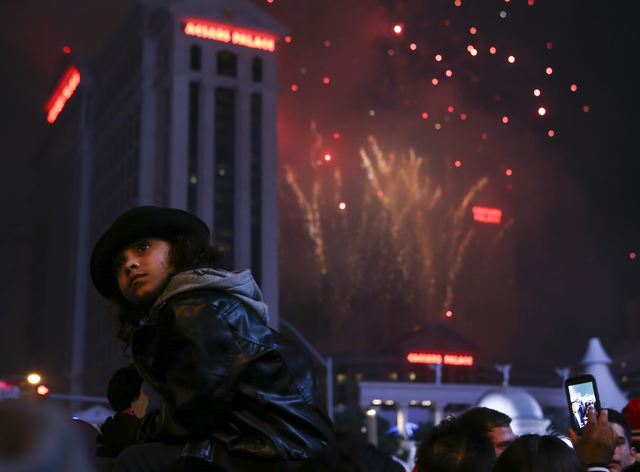 Eight-year-old Maria Washington watches fireworks go off as New Year's Eve revelers gather on the Las Vegas Strip on Sunday, Jan. 1, 2017. (Chase Stevens/Las Vegas Review-Journal) @csstevensphoto