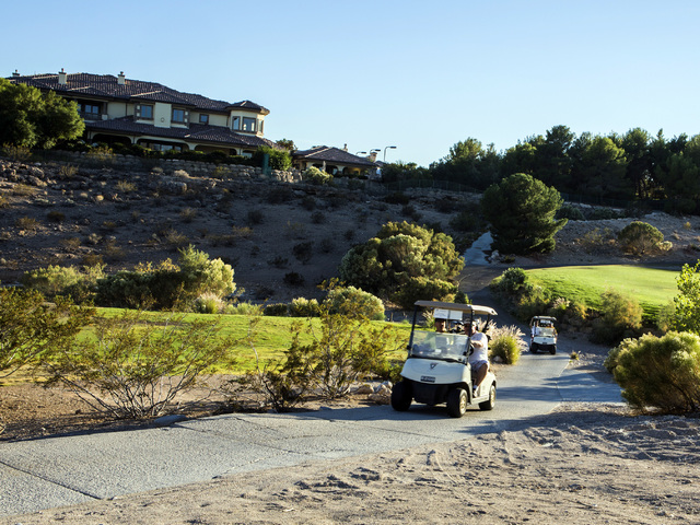 Golf carts travel along the trail at Badlands Golf Course on Wednesday, Oct. 9, 2016. Residents are concerned they will lose their views if the controversial, high-density development is approved  ...