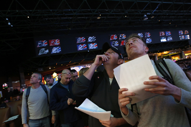 Betters who declined to give their name look at a tv screen while standing in line to place their bets at the Westgate sports book on Thursday, Jan. 26, 2017, in Las Vegas. (Christian K. Lee/Las V ...