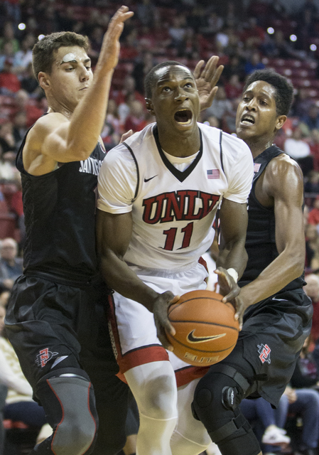 UNLV's Cheickna Dembele (11) splits San Diego State defenders Malik Pope (21) and Max Hoetzel (10) during the Rebels home matchup with the Aztecs on Tuesday, Jan. 17, 2017, at the Thomas & Mac ...