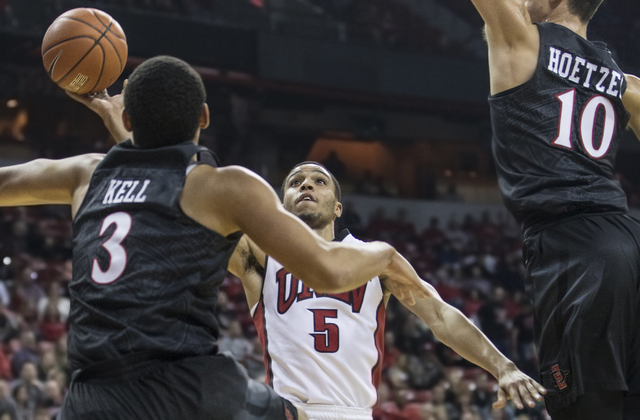 UNLV's Jalen Poyser (5) slices to the rim past San Diego State's Trey Kell (3) and Max Hoetzel (10) during the Rebels home matchup with the Aztecs on Tuesday, Jan. 17, 2017, at the Thomas & Ma ...