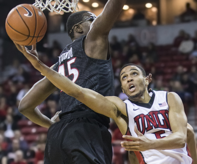 UNLV's Jalen Poyser (5) goes up and under the basket  past San Diego State's Valentine Izundu (45) during the Rebels home matchup with the Aztecs on Tuesday, Jan. 17, 2017, at the Thomas & Mac ...