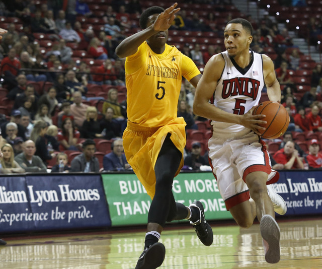 UNLV guard Jalen Poyser (5) drives towards the hoop pass Wyoming forward Alan Herndon (5) during the first half of a NCAA college basketball game against Wyoming at the Thomas & Mack Center on ...