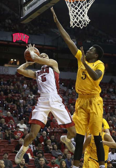 UNLV guard Jalen Poyser (5) makes a shot against Wyoming forward Alan Herndon (5) during the first half of a NCAA college basketball game against Wyoming at the Thomas & Mack Center on Saturda ...