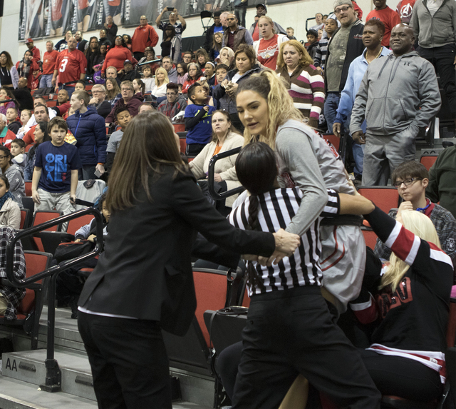 UNLV's forward Katie Powell calms down in the bleachers with head coach Kathy Olivier and a referee at the Cox Pavilion following a fight with Utah State's Antoina Robinson on Jan. 7, 2017. (Heidi ...