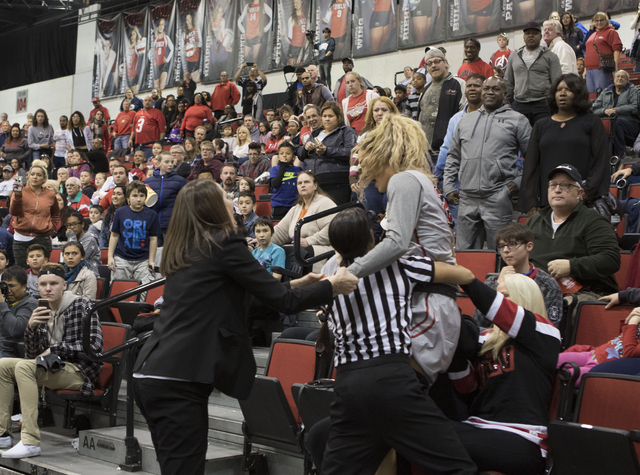 On Jan. 7, 2017, UNLV's Katie Powell is helped from the bleachers by Lady Rebels coach Kathy Olivier and a referee following a skirmish with Antoina Robinson at the Cox Pavilion. (Heidi Fang/Las V ...