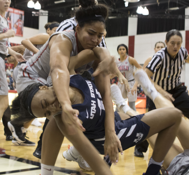 Lady Rebels' Paris Strawther tries to stop a fight between Utah State's Antoina Robinson and UNLV's Katie Powell during the third quarter of their game at the Cox Pavilion on Jan. 7, 2017. (Heidi  ...