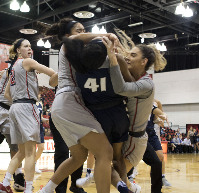 UNLV's Katie Powell (right) and Utah State's Antoina Robinson fall to the basketball court as they engage in a fight during the third quarter of their game at the Cox Pavilion on Jan. 7, 2017. (He ...
