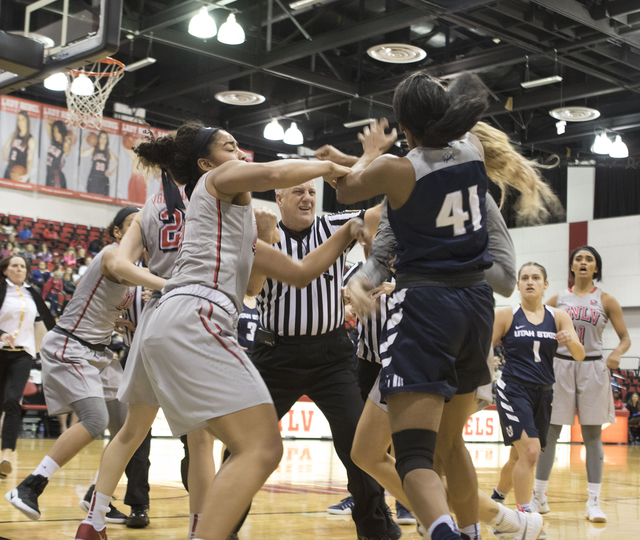 UNLV's Paris Strawther (left) attempts to stop a fight between Aggies Antoina Robinson and Lady Rebels Katie Powell during the third quarter of their game at the Cox Pavilion on Jan. 7, 2017. (Hei ...