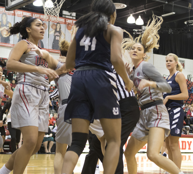 Lady Rebels forward Katie Powell (right) engages in a skirmish with Utah State's no. 41, Antoina Robinson, during the third quarter of their basketball game at the Cox Pavilion on Jan. 7, 2017. (H ...