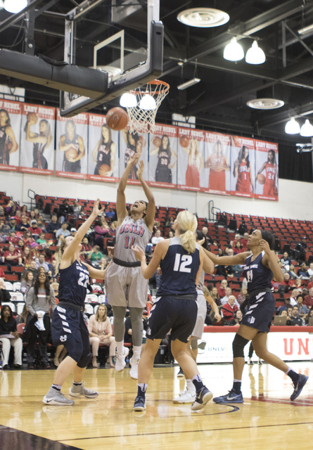Lady Rebels guard Dylan Gonzalez shoots a basket over Aggies defenders during the fourth quarter of their game at the Cox Pavilion on Jan. 7, 2017. (Heidi Fang/Las Vegas Review-Journal) @HeidiFang