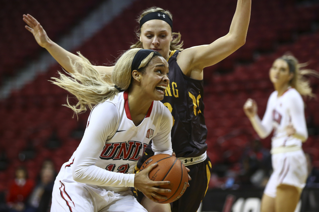 UNLV's Dakota Gonzalez (12) looks to shoot as Wyoming guard Hailey Ligocki (33) defends during a basketball game at the Thomas & Mack Center in Las Vegas on Wednesday, Jan. 25, 2017. UNLV won  ...