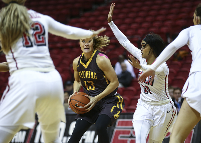 Wyoming guard Liv Roberts (13) looks to get past  UNLV defense, including UNLV's Dylan Gonzalez (11), during a basketball game at the Thomas & Mack Center in Las Vegas on Wednesday, Jan. 25, 2 ...