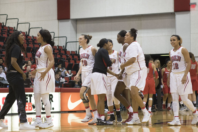 Lady Rebels players congratulate each other on their impending win late in the fourth quarter. (Heidi Fang/Las Vegas Review-Journal) @HeidiFang