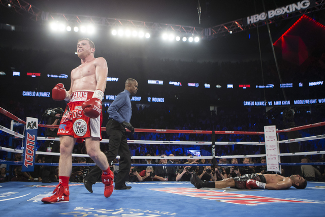 """Saul """"Canelo"""" Alvarez, left, walks to a corner after knocking out Amir Khan in the sixth round of the WBC Middleweight Title bout at the T-Mobile Arena on Saturday, May 7, 2016, in L ..."""