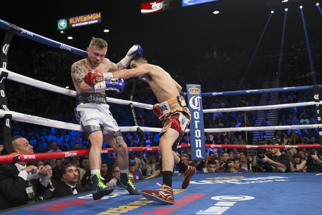 Leo Santa Cruz, right, connects a punch against Carl Frampton in the WBA Featherweight Championship bout at MGM Grand Garden Arena on Saturday, Jan. 28, 2017, in Las Vegas. Santa Cruz won by split ...