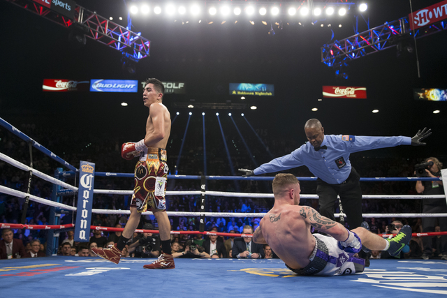 Carl Frampton, right, slips to the ground in his fight against Leo Santa Cruz in the WBA Featherweight Championship bout at MGM Grand Garden Arena on Saturday, Jan. 28, 2017, in Las Vegas. Santa C ...