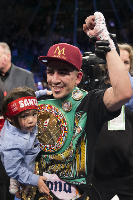 Leo Santa Cruz, holding his son Alan, 2, celebrates his split decision win against Carl Frampton in the WBA Featherweight Championship bout at MGM Grand Garden Arena on Saturday, Jan. 28, 2017, in ...