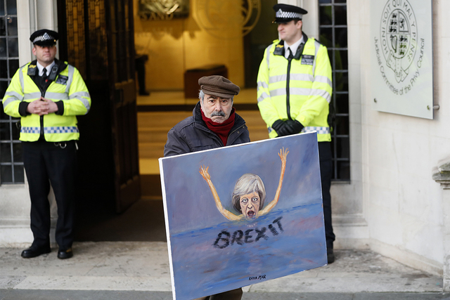 Painter Kaya Mar shows his latest painting of British Prime Minister Theresa May in front of the Supreme Court in London, Tuesday, Jan. 24, 2017. Britain's Supreme Court ruled Tuesday that Parliam ...