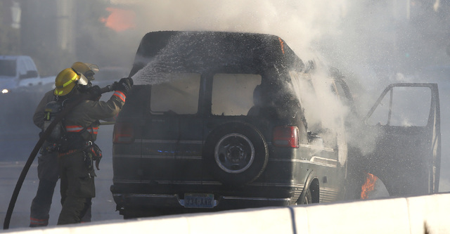 Firefighters rush to put out a vehicle engulfed in flames on I-15 south near exit 37 on Saturday, Jan. 28, 2017, in Las Vegas.
