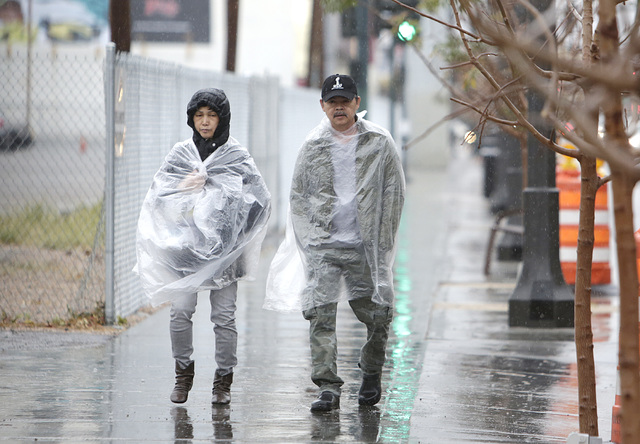 Pedestrians wear plastic raincoats to protect themselves from the rain as they walk along Main Street on Friday, Jan. 13, 2017, in Las Vegas.  (Bizuayehu Tesfaye/Las Vegas Review-Journal) @bizutesfaye