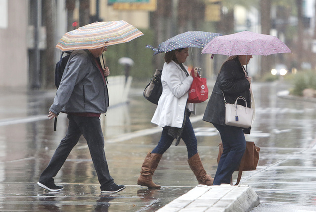Pedestrians hold umbrellas to protect themselves from the rain as they cross Louis Avenue on Friday, Jan. 13, 2017, in Las Vegas. Friday started with rain in the area, but that will taper off thro ...
