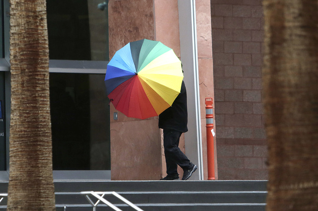 A man holds an umbrella to protect himself from the rain walks near the Regional Justice Center on Friday, Jan. 13, 2017, in Las Vegas. Friday started with rain in the area, but that will taper of ...