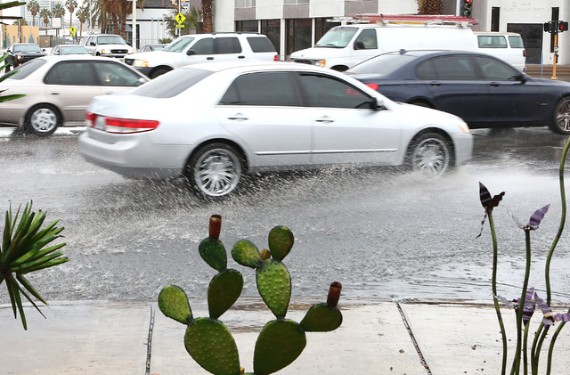 Motorists navigate through a flooded street on Charleston Boulevard Friday, Jan. 13, 2017, in Las Vegas. Friday started with rain in the area, but that will taper off throughout the day. (Bizuayeh ...