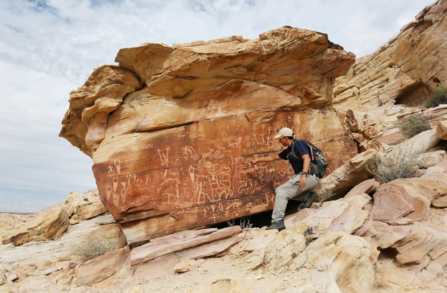 Jose Witt, southern Nevada director of Friends of Nevada Wilderness, points out petroglyphs while leading a hike Sunday in Gold Butte. (Ronda Churchill for The Washington Post)