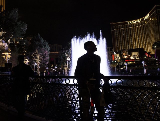 Tyler Humes enjoys the fountain outside the Wynn hotel-casino on the Strip on New Year's Eve in Las Vegas. (Benjamin Hager/Las Vegas Review-Journal)