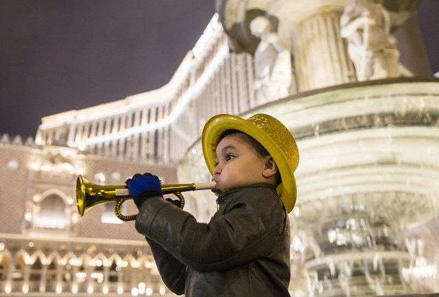 Justin Alcantara, 5, plays a miniature trumpet outside the Venetian hotel-casino on New Year's Eve in Las Vegas. (Benjamin Hager/Las Vegas Review-Journal)