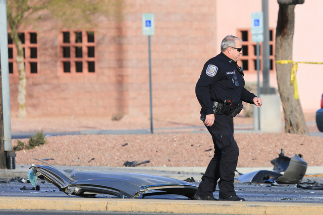 A North Las Vegas police officer walks past the roof of a Ford Taurus that was cut off at the scene of a crash on Martin Luther King Boulevard near Carey Avenue on Friday, Jan. 6, 2017. Brett Le B ...