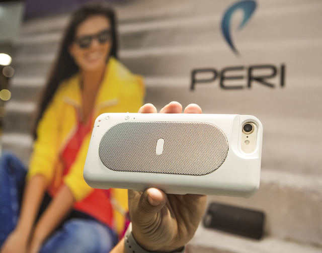 Erica McCarthy hold the Duo Slim 2-in-1 speaker and fast-charging battery case for the Apple I-phone during CES 2017 in the Las Vegas Convention Center on Friday, Jan. 6, 2017. Around 175,000 peop ...